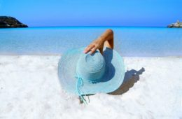 Frau mit Hut am Sandstrand - EYVA Blog