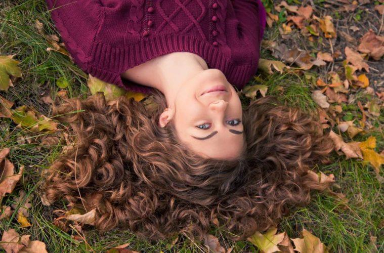 Frau auf Wiese mit Herbstlaub liegend - (c) shutterstock.com